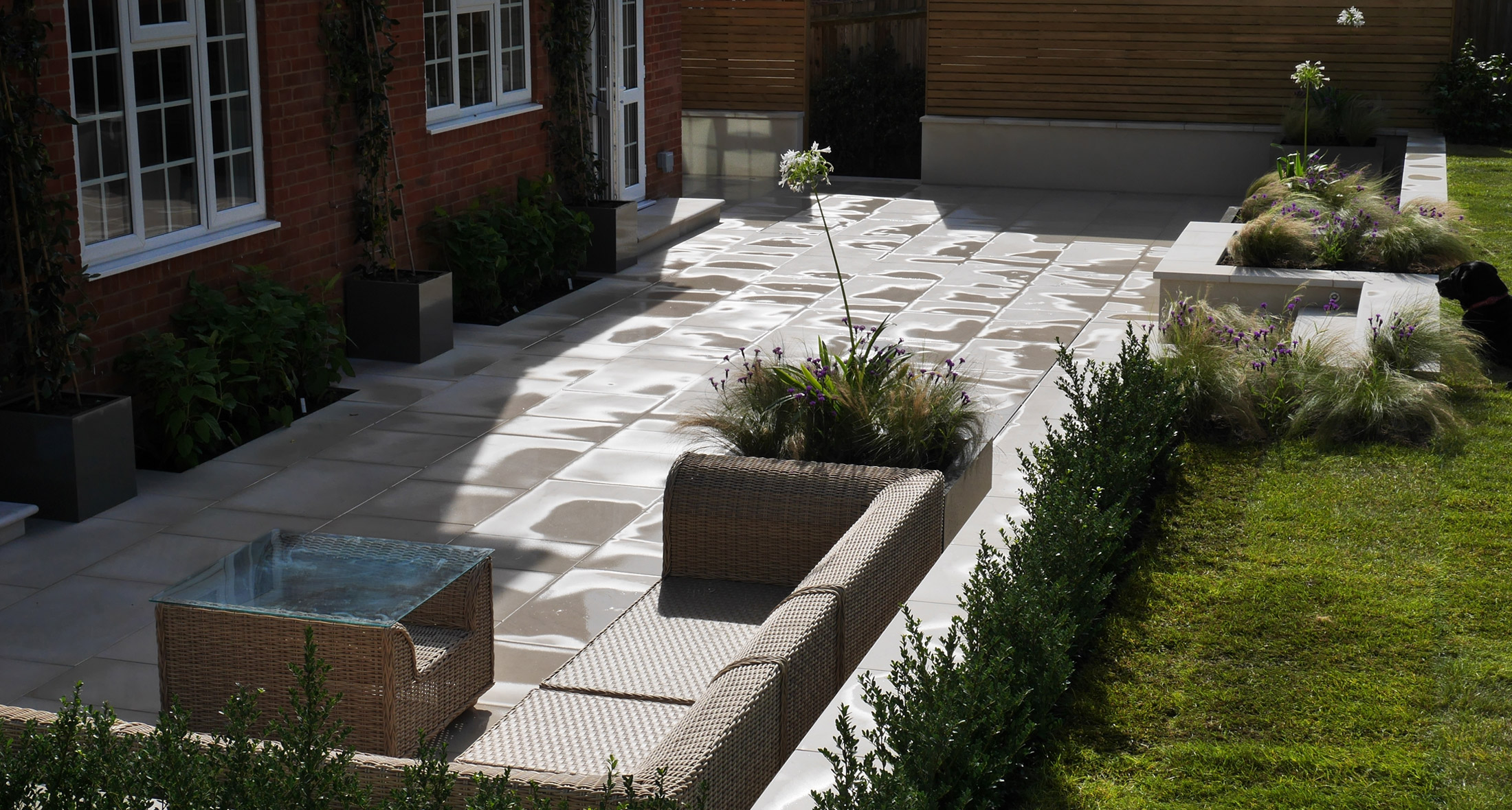 a slate grey garden design and landscaping patio with sleek grey paving and surrounding raised planting