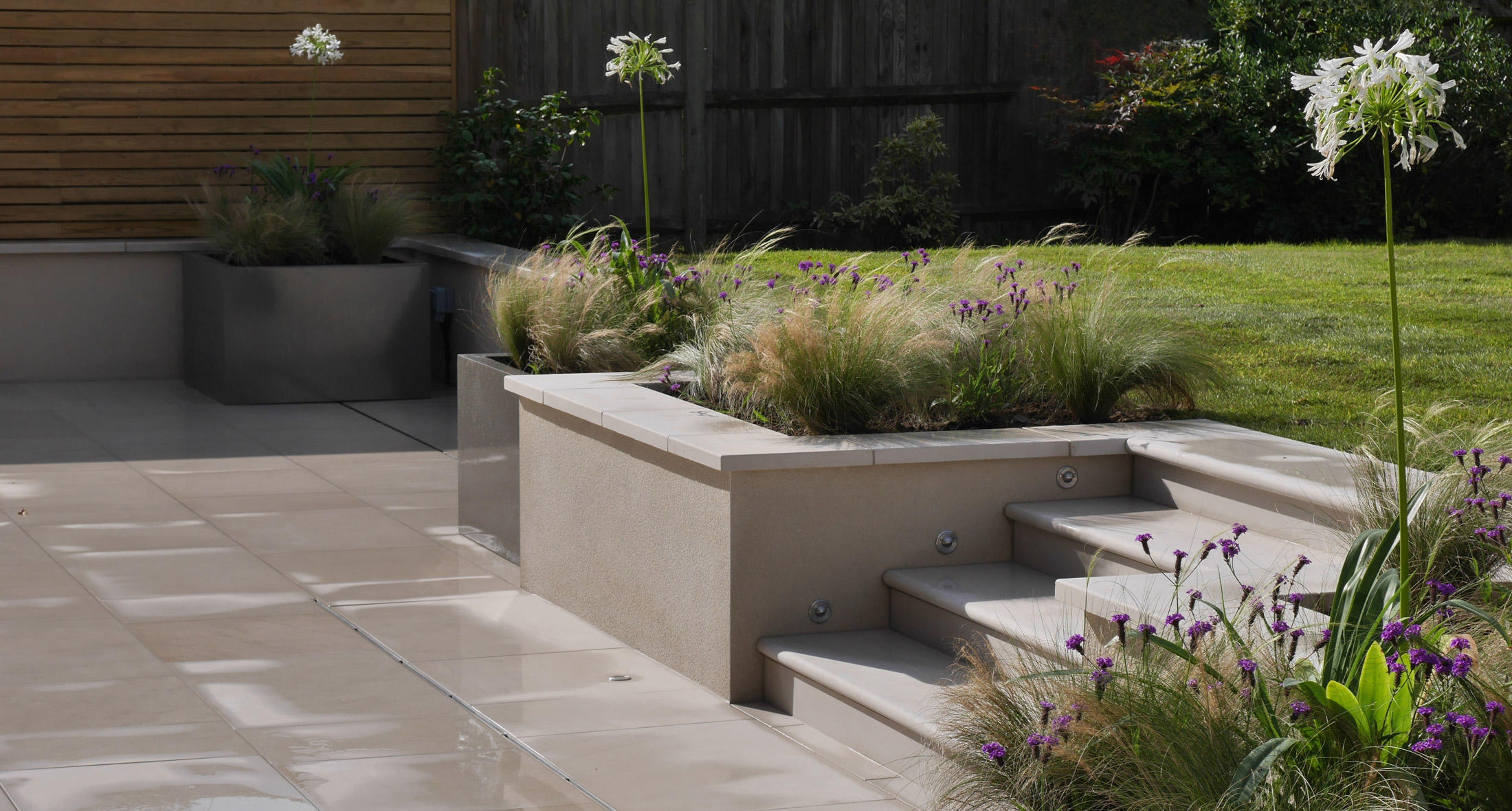 a slate grey garden design landscaping patio showing raised edging and containers - Garden Design Uk